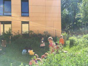 Kinder säen Wilblumen im Schulgarten.
